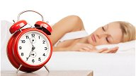 wind up alarm clock with girl sleeping